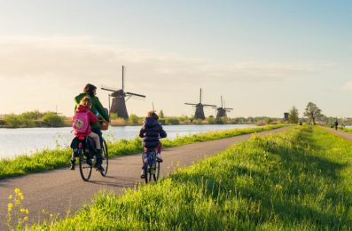 Kinderdijk, The Netherlands - Rear view of a woman and two children as they cycle along a canal path lined with traditional Dutch windmills.